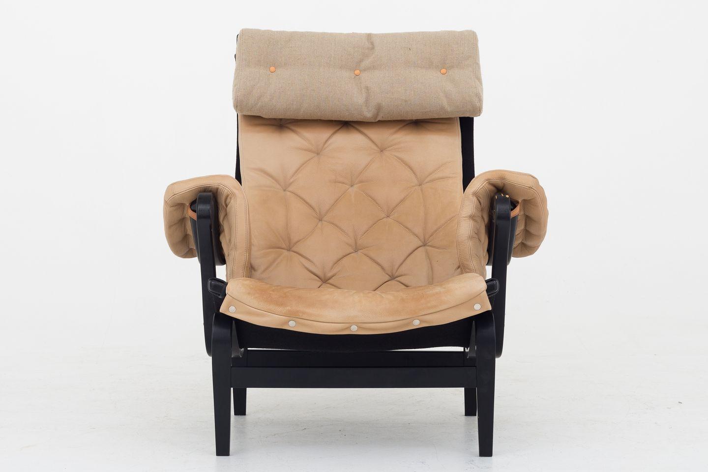 Bruno Mathsson Dux Pernilla 69 lænestol i sortlakeret træ med hynder i lyst læder og nakkepude i kanvas 1 stk. på lager Brugt stand Lokation: Roxy