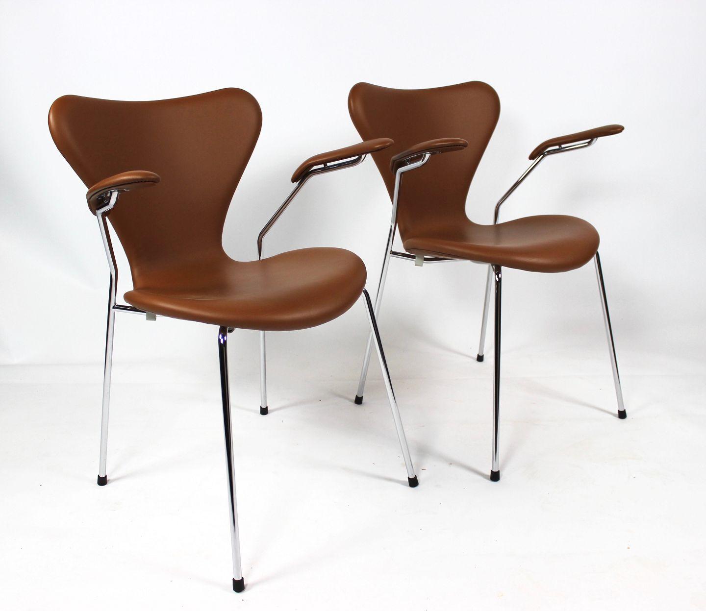 Et sæt af syver stole, model 3207, med armlæn i cognac farvet læder af Arne Jacobsen og Fritz Hansen. 5000m2 udstilling.